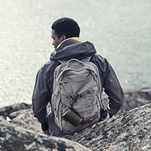 Beosound Explore speaker hanging on a backpack while hiking