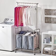 washing machine, laundry sorter, attached bar holding clothes, white shelf in a laundry room setting