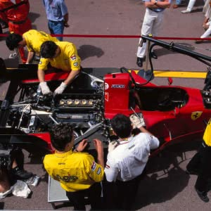 A pit crew working on the engine of a red race car.