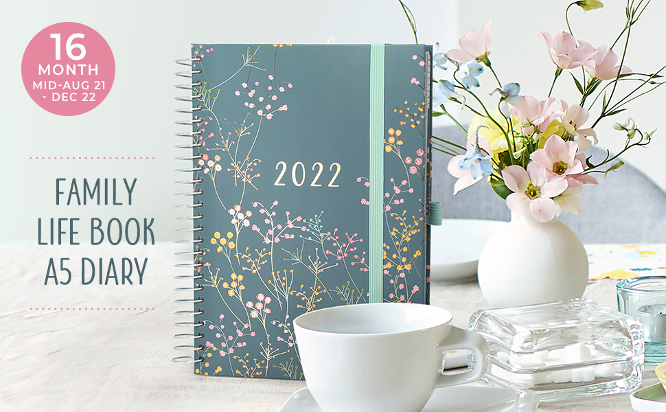 The Family Life Book Diary stood on a table behind a cup and saucer, next to a vase of flowers