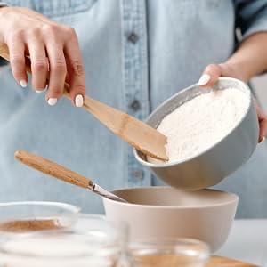 mains de femme avec un bol de farine de coco
