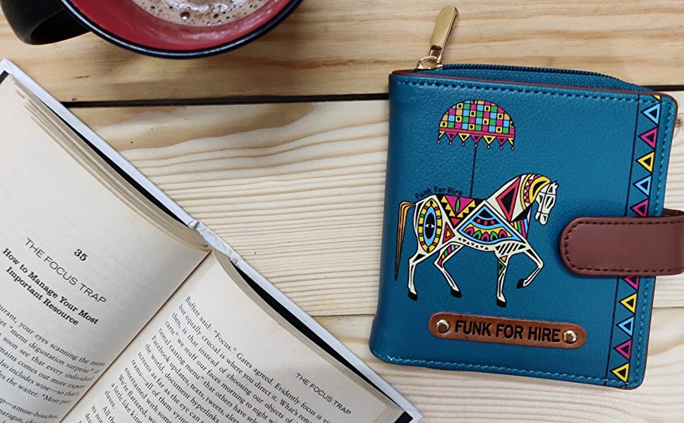 Horse Printed Loop wallet on desk along with a cup of coffee and a book