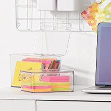 Small Clear Plastic Storage Boxes Holding Colorful Office Supplies on Desktop Next to Laptop