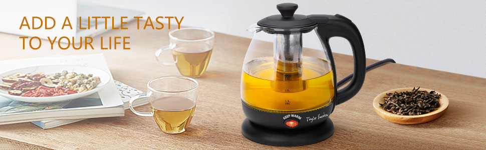 There is an electric kettle, two cups of tea and tea leaves on the table.