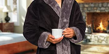 Man with hands in pockets wearing robe and drinking coffee
