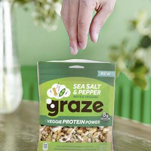 Een hand met de zak van de noten mix van graze, met cashews, erwtjes tuin en edamame bonen