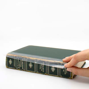 Hand applying clear poly BookGuard tape to old book spine