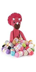 assortment of amigurumi select bonbon mini balls of yarn arranged in front of an amigurumi doll