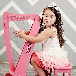 Little girl playing the schoenhut pink lyre harp