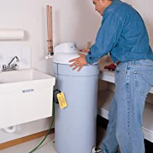 Water softener being installed against a wall next to a sink.