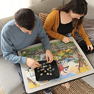 A couple doing their 1,000 piece puzzle on the couch