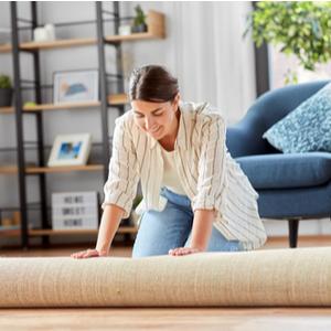 Woman unrolling indoor area rug in living room