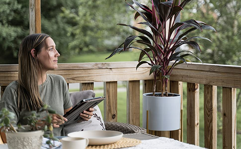 Woman looks at white planter