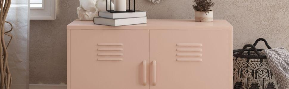 Pink metal locker storage accent cabinet with two doors with books, candle and decorations on top.