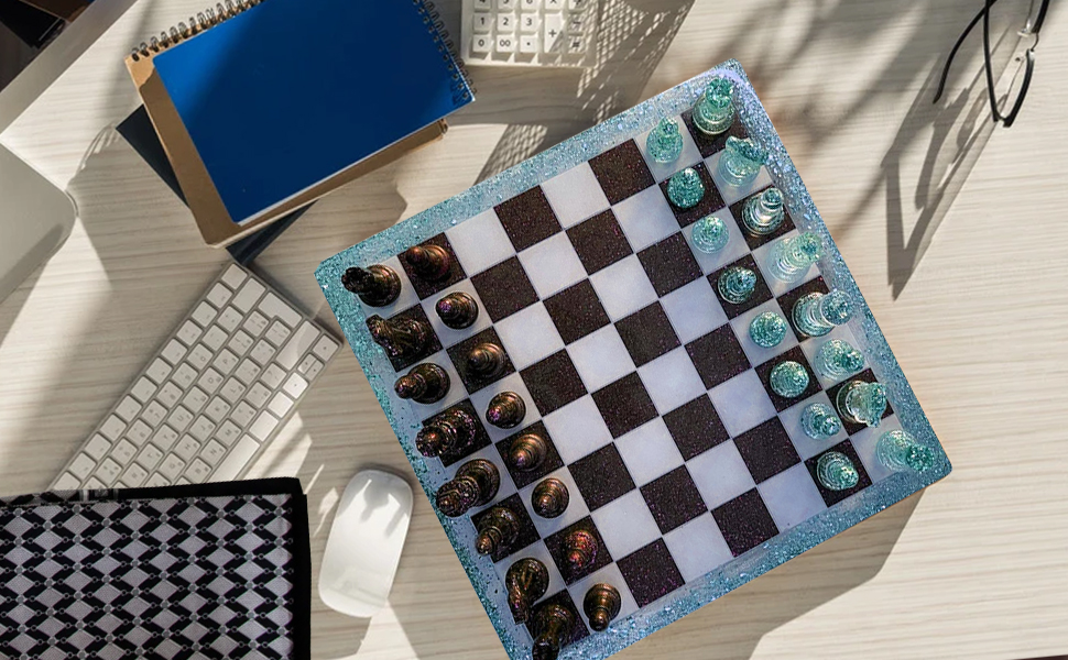 There are keyboards, notebooks, resin chessboards and resin chess pieces on the desktop