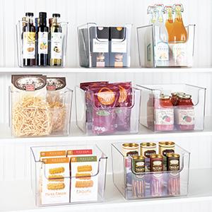 clear plastic bins holding bottles, jars, pasta, snacks on shelves, white pantry setting