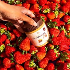 ChocZero White Chocolate Hazelnut Spread held over strawberries.