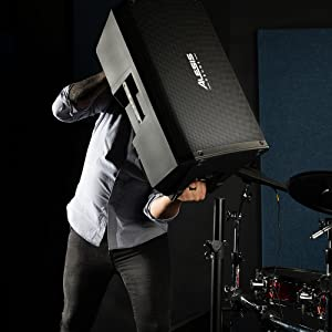 A MAN CARYING THE ALESIS STRIKE AMP 12