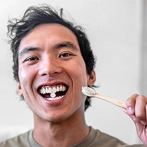 Man holding tablet in teeth.