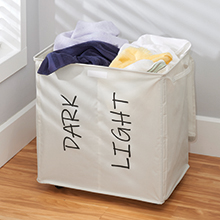 filled cream fabric divided laundry hamper, labeled dark and light in corner, gray wall, wood floor