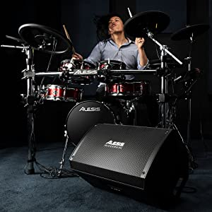 A MAN PLAYING ON THE ALESIS SRUMPS WITH CONNECTED ALESIS STRIKE AMP 12
