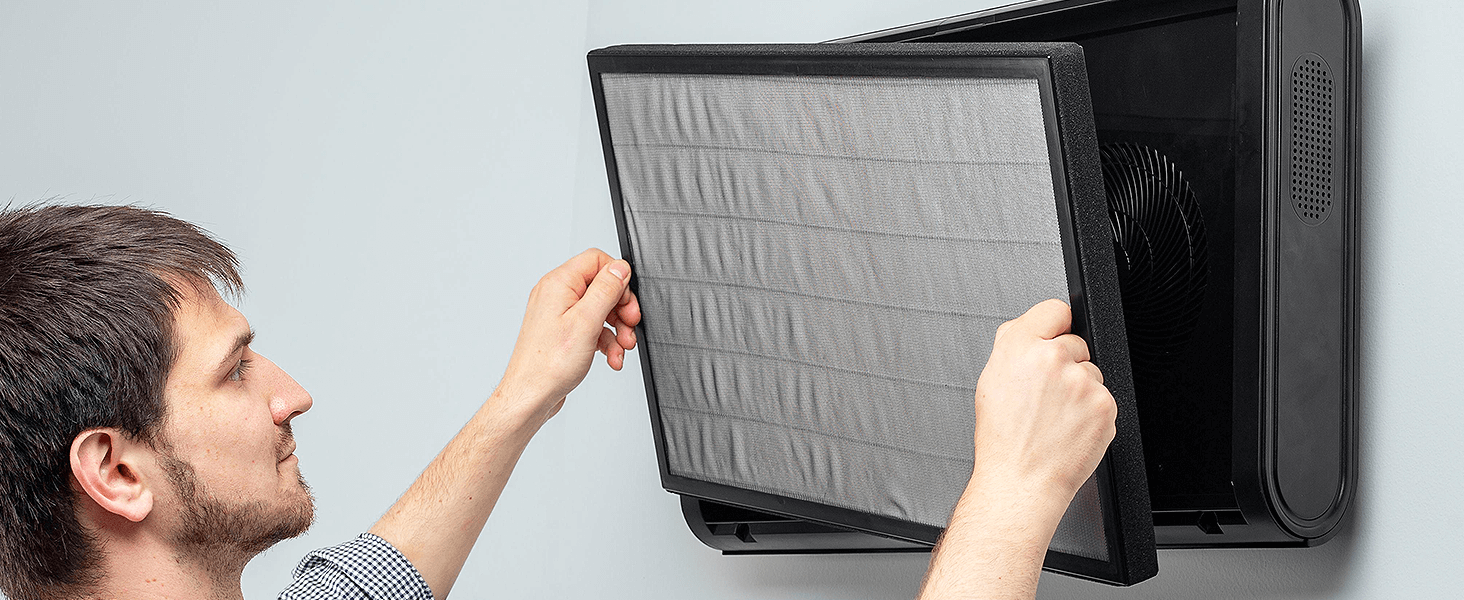 Man changing a black MA-35 filter mounted on a wall