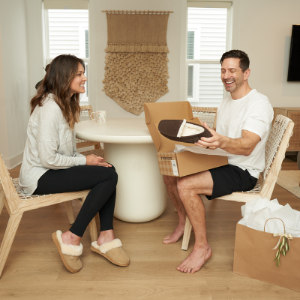 Man opening a giftbox with the melbourne moccasin slipper