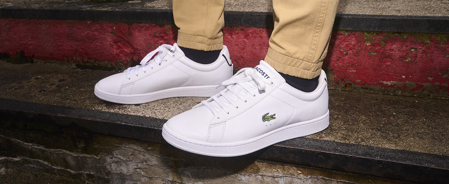 Weißer Sneaker mit aufgesticktem grünen Lacoste-Krokodil