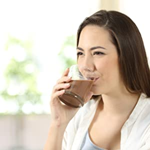 Woman drinking a chocolate protein pudding shake