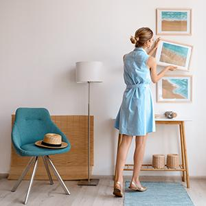 Woman decorating her home and hanging photos, lamp with finial in background