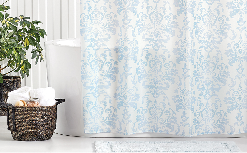 Brown basket, white tub and blue and white shower curtain and plant in a bathroom setting