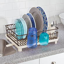 bronze dish drying rack holding dishes on marble counter, drain spout, water dripping into sink