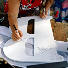 An Unfinished Wood Co 23 Inch Letter B, being used as a guestbook