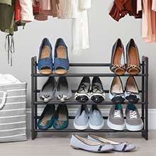 3 tier black shoe rack holding shoes with hamper on side and clothes above in a closet setting