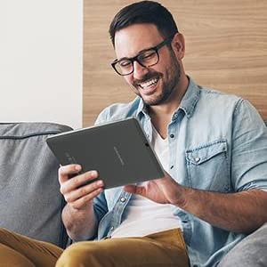 A man sit on sofa playing the Vastking tablet