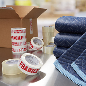 blue shipping blankets, clear packing tape, fragile tape with text in red, open brown box