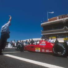 A person marking the beginning of a race next to a red race car on a track.