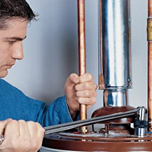 Gas-fired water heater being repaired with a socket wrench.