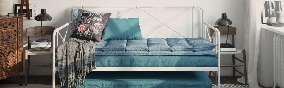 Bedroom with white metal daybed and trundle, blue mattresses and geometric accents on back and sides