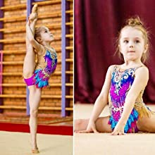 A lovely kid is training with the beautiful rhythmic gymnastics leotards