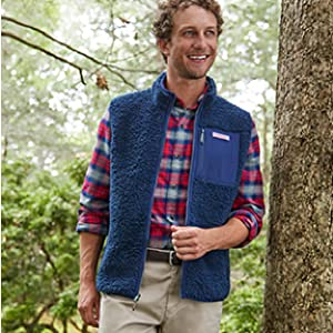 Man wearing vineyard vines plaid button up and blue vest standing in the woods.