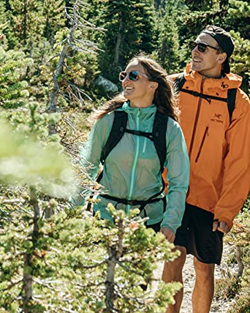two hikers wearing Zeal sunglasses walking through pine trees