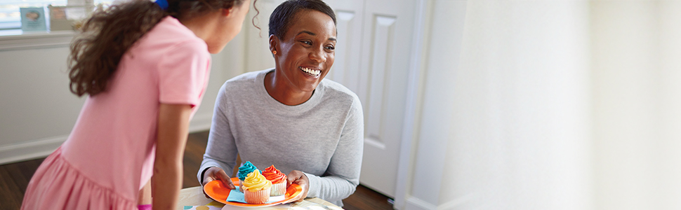 Daughter with mom smiling and holding a plate of colorful cupcakes at a celebration