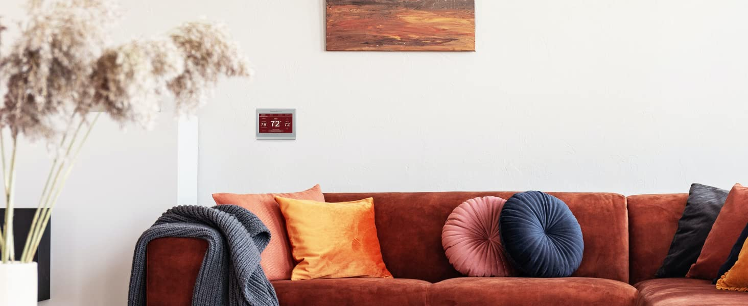 Wifi smart color thermostat with red screen above a red couch