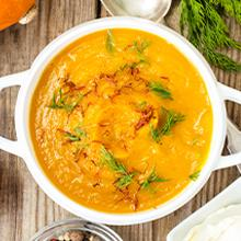 A bowl of homemade pumpkin soup with curry, saffron and cheese balls on a wooden dinner table