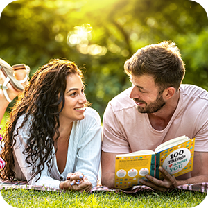 """Photo of couple laying on the grass enjoying """"100 Things I Love About You""""."""