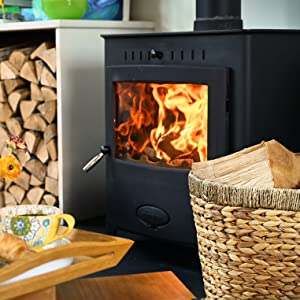 Close up of a stove with a log basket in front