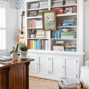 Photo of bookshelf in home office with colorful books