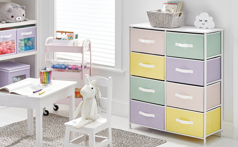 nursery setting, white table, storage unit, multi colored fabric drawers, crayons, books, toys