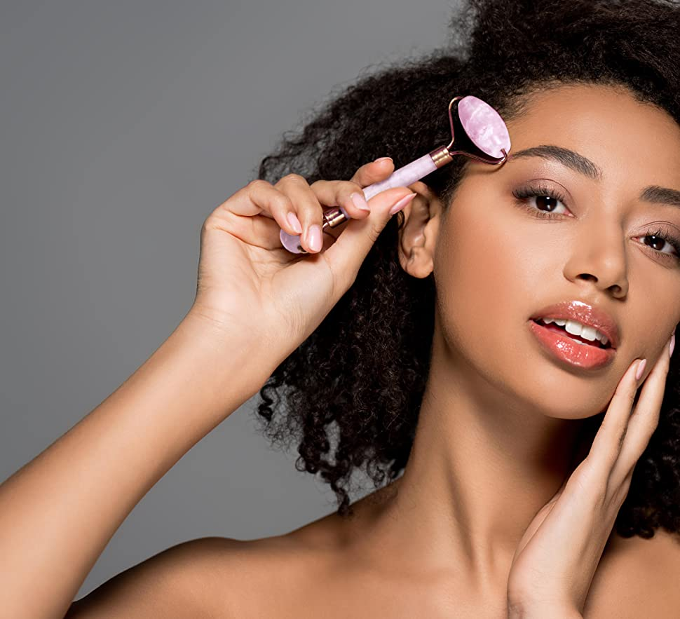 A beautiful mixed race girl holding the rose quartz roller to her face